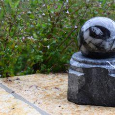 Schwarze Marmorkugel mit Sockel als Wasserspiel